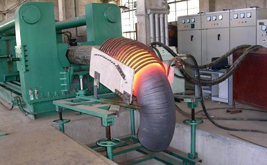 Mid-frequency extruding machine for the forming of nickel alloy elbows.